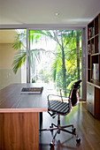 Desk and swivel chair in study with glass sliding wall