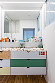 Terrazzo sink and washstand top on base unit with multicoloured drawers