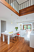 White dining table in open-plan kitchen