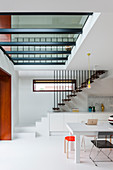 Staircase in white, open-plan kitchen