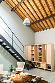 Shelves used as partition at foot of staircase in interior with high ceiling