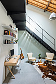 Desk and seating area with retro armchairs below metal staircase