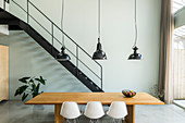 Three ceiling lamps above dining table in front of black metal staircase