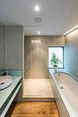 Modern bathroom with clear lines, grey walls and bathtub
