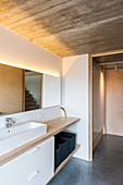 Bathroom with indirect lighting, concrete ceiling and fitted furnishings