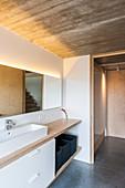 Bad mit indirekter Beleuchtung, Betondecke und Einbaumöbeln