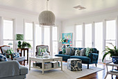Light-flooded living room with blue upholstered sofa and blue and white striped armchairs