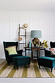 Wing chair with matching footstools, side table and ladder against white cassette wall