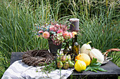 Autumn arrangement with pumpkins, pears and flower arrangement on the garden table