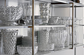 Collection of crystal glassware on glass shelves