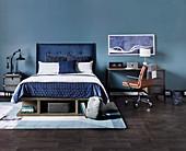 Doppelbett mit blauem Betthaupt, daneben Schreibtisch mi Lederstuhl vor blauer Wand