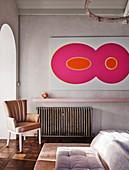 Retro Lederstuhl vor Heizkörper und moderne Kunst an der Wand