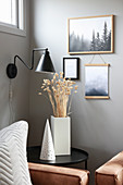 Black side table and wall-mounted lamp in corner