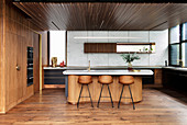 Kitchen island with marble top and bar stools in an open kitchen with wooden paneling