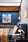 Double bed in front of wooden wall in concrete look in the bedroom, artwork on a blue wall in the background