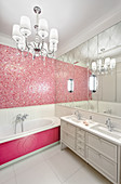 Pink mosaic wall and bathtub surround in vintage-style bathroom