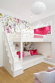 Loft bed with storage solutions against floral wallpaper