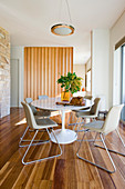 Round table with marble top and pale chairs in dining area with slatted wooden partition in background