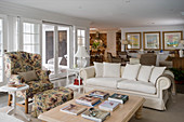 White sofa, armchair with colourful upholstery and matching footstool around coffee table in open-plan interior