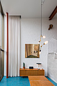 Retro sideboard against brick wall in double-height interior