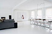Grey sofa and long dining table in open-plan interior decorated entirely in white