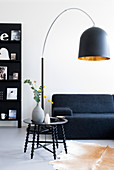 Black arc lamp above sofa and coffee table in living room