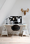 Black shell chair at desk on trestles below sloping ceiling