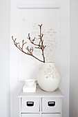 Twig in white case in front of roll of paper with cut-out pattern hung on wall
