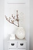 Zweig in weißer Vase vor einer Papierrolle mit Cut Outs