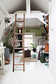 Ladder leading to bed below ceiling in small room decorated in vintage style