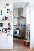 Kinderbilder an der Wand, Blick in die Küche mit Edelstahlherd