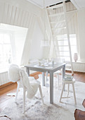 Small dining table and various chairs in white interior