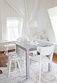 Kleiner Esstisch mit verschiedenen Stühlen in weißer Ambiente