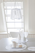 Place setting on dining table below pendant lamp in white interior