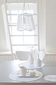 Esstisch mit einem Gedeck, darüber Hängelampe in weißer Ambiente
