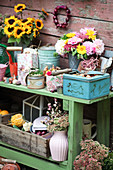 Vintage accessories, autumn flowers and gardening utensils on green potting table