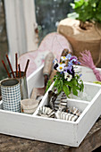 Posy of spring flowers and craft materials in organiser crate
