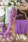 Cords and yarn in shades of purple, cow parsley and chive flowers
