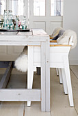 Sheepskin rugs on rustic chairs at pale grey wooden table
