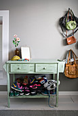 Stack of colourful sneakers on base of pale green console table against grey wall