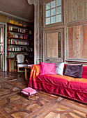 Sofa with scatter cushions and throw in shades of red on antique parquet floor