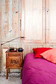 Bett mit Wäsche in Pink und Rot vor einem Wandschrank aus Holz