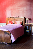 Antique bed with carved headboard and foot against pink bedroom wall