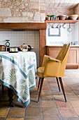 Yellow armchair in rustic kitchen-dining room with terracotta floor tiles