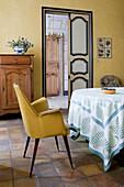 Gelber Polsterstuhl am Tisch im mediterranen Esszimmer mit Terracottafliesenboden