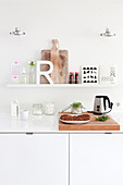 Letter R and chopping board on picture ledge above worksurface in white kitchen