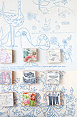 Small square pictures on blue-patterned wallpaper