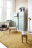 Retro armchair in front of two tall chests of drawers in vintage-style living room