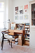 Sheepskin rug on chair at desk below pictures on wall