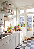 White kitchen with chequered floor and balcony doors